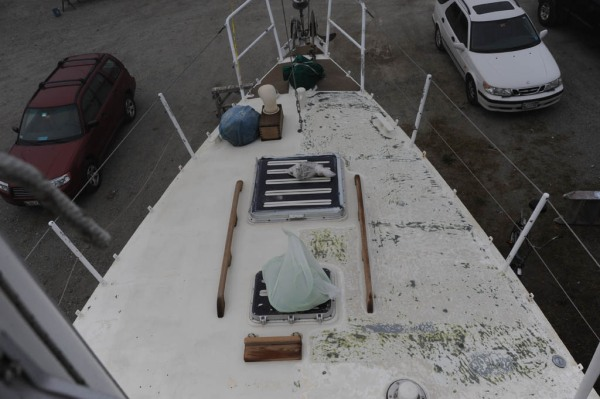 A colorful 30-year history of deck paint unfolds as grinding begins on the starboard side.