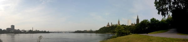 Colline du Parlement (Parliament Hill) rising above the banks of the Ottawa River. - Composite image