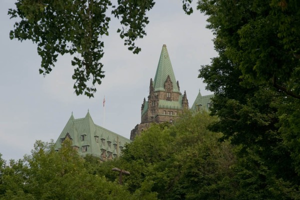 Parliament Buildings peeking through the trees of the Colline du Parlement, Ottawa.