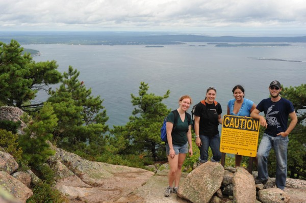 "Brittany, Eugenia, Adri and I pose next to the ""Caution: Climbing the Precipice may kill you!"" sign."