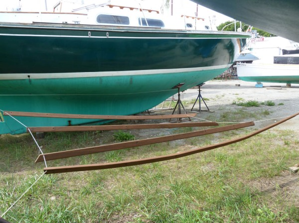 The toe-rails hanging between neighboring boats after the third and final coat of varnish (Sikkens Cetol).