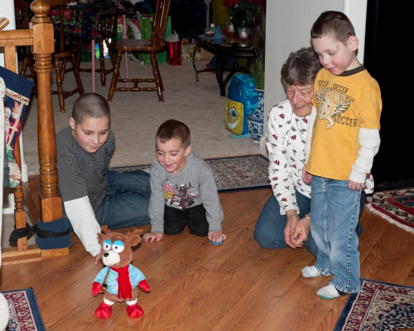 Gage, Jace, Mom, and Tayt watch the dancing Christmas Bear Reindeer Creature.