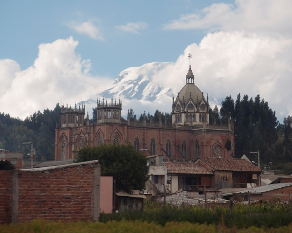 View from the bus window: Chimborazo rises behind a church near Riobamba.