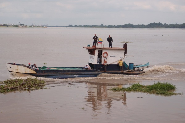 A workboat chugs upstream on the Guayas River.