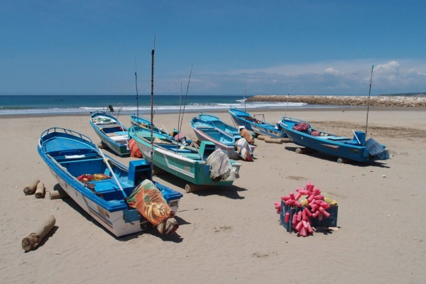 Fishing boats and nets lined up on the beach.
