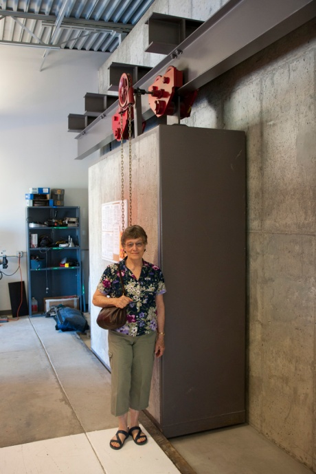 Mom stands next to a really big door used to shield the outer areas of the laboratory from radiation.