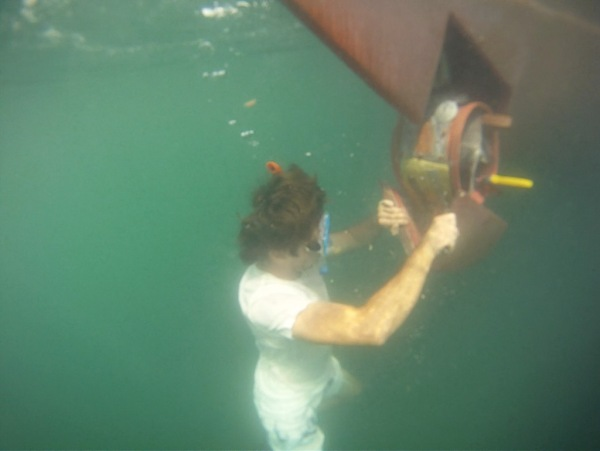 Nicolas and I preparing to use an underwater drill to re-secure the bow thruster fairing to its housing.