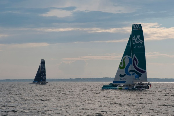 MOD70 trimarans racing out the Newport channel.
