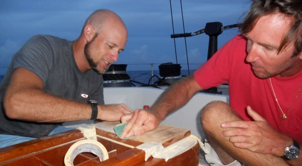 Boat work never ends, even while on a passage! Nicolas and I sanding the teak cockpit table on a calm night at sea.