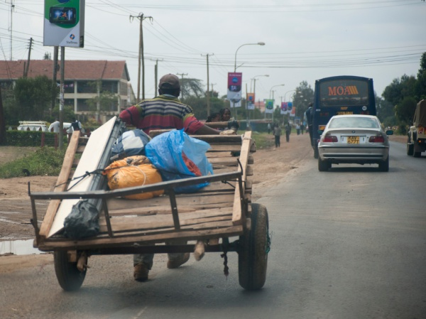 Passing a mkokoteni (hand-pulled cart) while leaving Nairobi. Somewhat of a contrast to the BMW just ahead.
