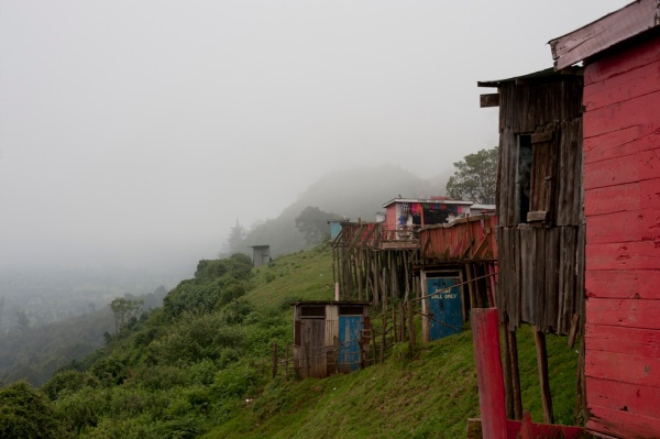 Houses and tourist shops line the roadside viewpoint.