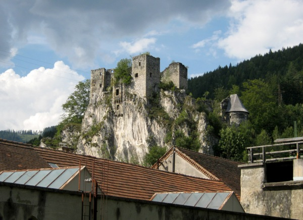 The ruins of Schachenstein Castle rise over a factory in Thörl.
