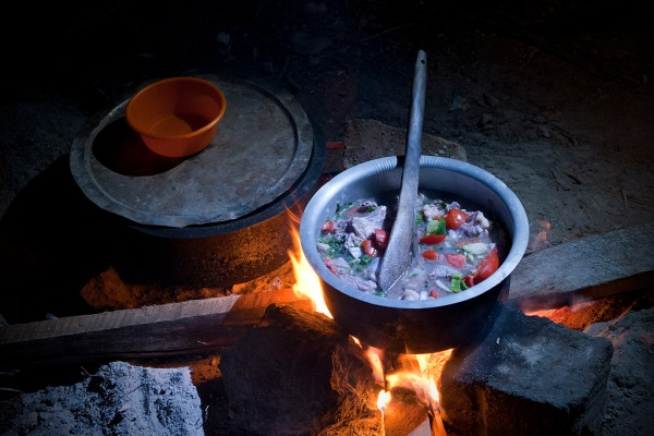 A delicious goat stew in the works over the campfire.