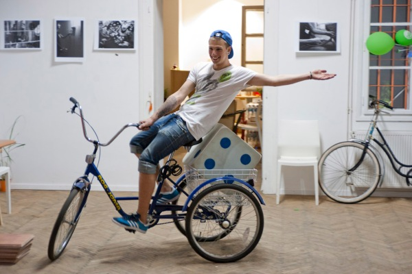 Tameo rides a tricycle around the Moj Bicikl Bike Info Center.