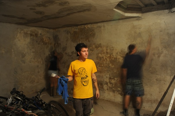 Re Mić considers what to paint next while Tamina and Tameo work on re-plastering the walls of the Center's basement.