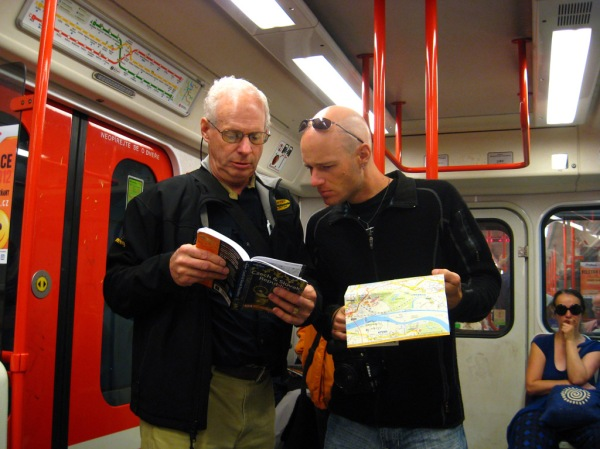 "Dad and I reading the chapter titled ""How Not to Look Like Tourists"" while riding the metro."